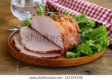 roast pork with paprika and rosemary served on a wooden plate