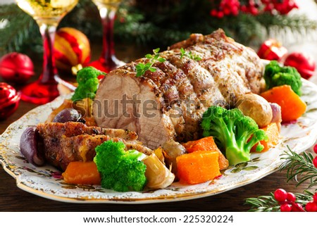 Roast pork with vegetables and spices. - stock photo