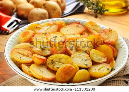 Roast potatoes. Oven-roasted, sliced potatoes with herbs (thyme and rosemary) and olive oil.