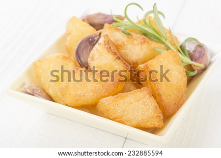 Roast Potatoes - White potatoes roasted with garlic and rosemary in goose fat on a white background.