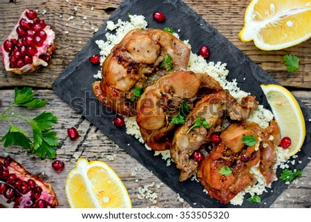 Roast rabbit with couscous in oriental style on old wooden table - stock photo
