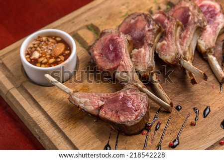 Roast rack of lamb served on wooden board - stock photo