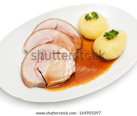 Roast suckling pig with potato dumplings on white background