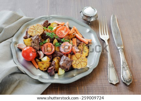 Roast venison with vegetables on a vintage pewter plates, linen napkin and old cutlery on a wooden table