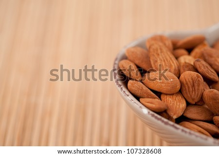 Roasted almonds in a bowl on a wooden placemat