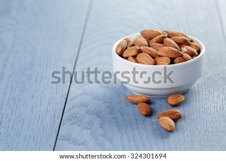 roasted almonds in white bowl on blue wooden table - stock photo