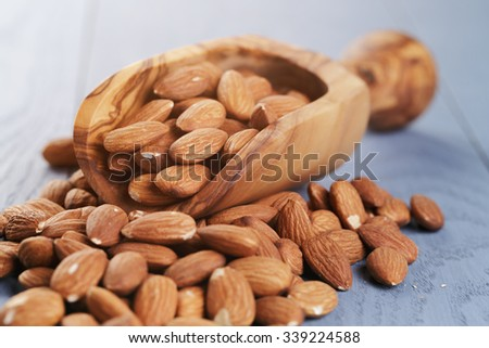 roasted almonds on blue wooden table with scoop, selective focus