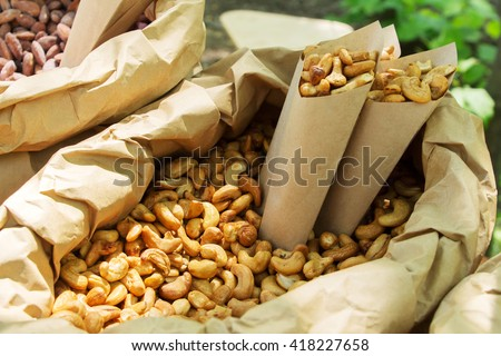 roasted almonds, pine nuts, hazelnuts, cashews and peanuts in sugar syrup with different tastes in paper envelope at festival of street food. Healthy diet. - stock photo