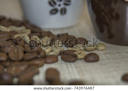 Roasted and raw coffee beans on a wooden base