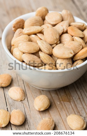 Roasted and salted almonds in a bowl - stock photo