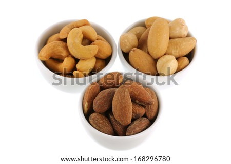 Roasted and salted Cashew nuts, Brazil nuts and Almonds in white bowl, isolated on white - stock photo
