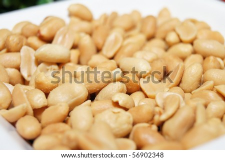 Roasted and salted peanuts on white bowl