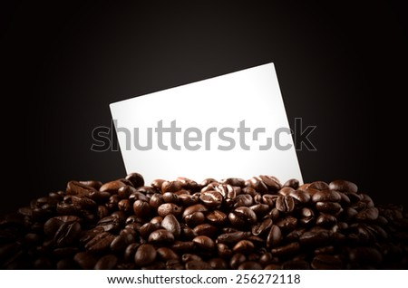 Roasted Arabica coffee beans and a plain white paper for your texts. - stock photo