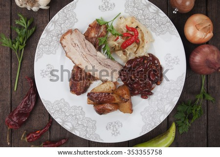 Roasted bacon or pork belly with sauerkraut, kidney beans and baked potato - stock photo