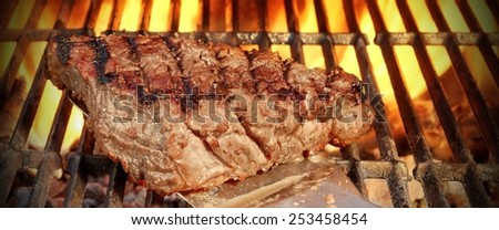 Roasted BBQ Beefsteak on the Spatula Over a Hot Charcoal Grill, Flames of Fire on the Black Background. - stock photo