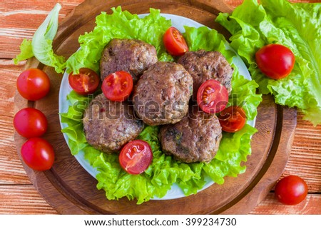 Roasted beef cutlets, green salad and small tomatoes on white plate. Wooden background. Top view. - stock photo