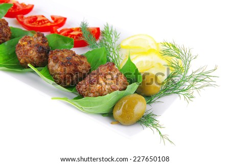 roasted beef cutlets on white with tomatoes and lemon - stock photo