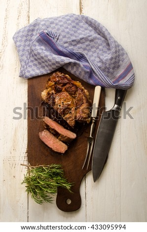 roasted beef shoulder with meat fork and knife and rosemary on wooden board