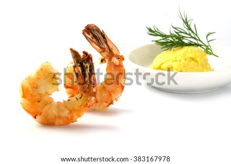 roasted black tiger prawns, garlic dip blurred in the background, finger food appetizer on a festive party, closeup shot isolated with shadows on white, selected focus, narrow depth of field - stock photo