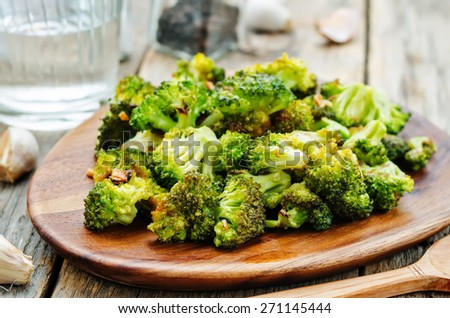 roasted broccoli with garlic on a dark wood background. the toning. selective focus - stock photo