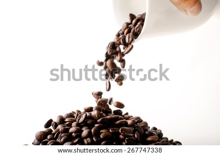 Roasted brown coffee beans falling isolated in white background - stock photo