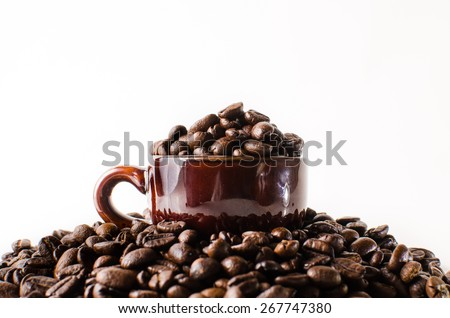 Roasted brown coffee beans & mug  in isolated white background - stock photo