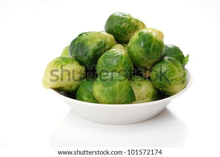roasted brussels sprouts on a white plate, studio isolated - stock photo