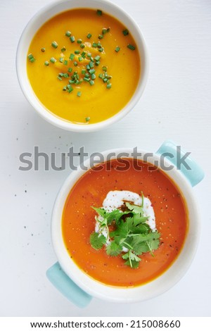 Roasted butternut pumpkin squash soup and a tomato sweet potato soup garnished with coriander and coconut milk cream - stock photo