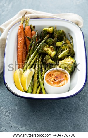 Roasted carrots, asparagus and broccoli with a dip - stock photo