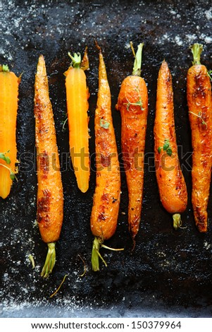 roasted carrots with spices on a baking tray, food - stock photo