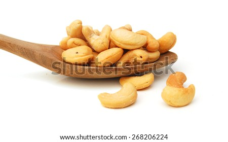Roasted cashew nuts in wooden spoon on white background  - stock photo