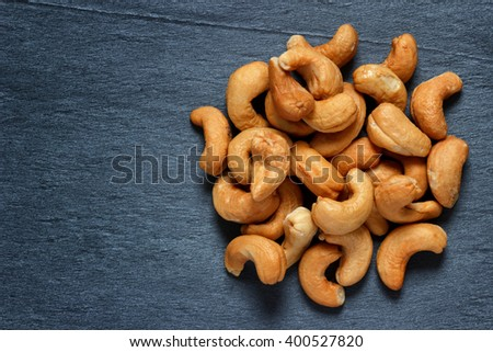 Roasted cashews on dark stone background