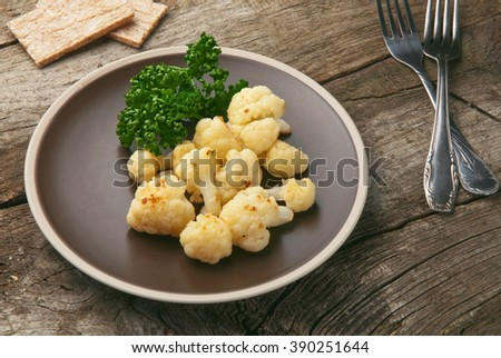 roasted cauliflower with parsley leaves on brown plate on a gray wooden background closeup. Healthy food