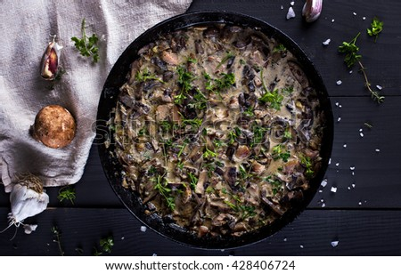 Roasted  champignons mushrooms with meat, butter, parsley and roasted garlic in black bowl. Selective focus. Healthy food concept. - stock photo