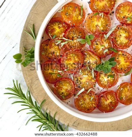 Roasted cherry tomatoes in white pan over rustic timber.  Top view. - stock photo