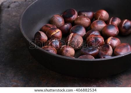 Roasted chestnuts in a pan - stock photo