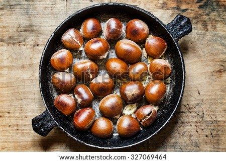 Roasted chestnuts in a pan, selective focus - stock photo