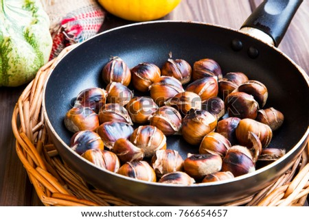 Roasted chestnuts in a pan top view with autumn dried leaves , cones and pumpkins, fall food , edible chestnuts