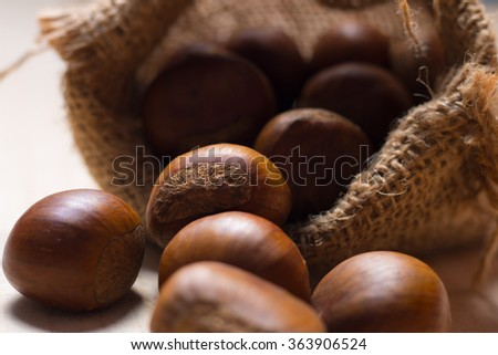Roasted chestnuts in sack on wooden table - stock photo