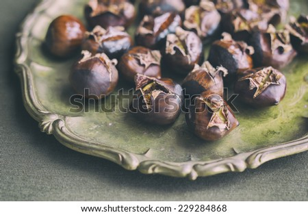 Roasted chestnuts on a brass serving platter against an olive green background.  Analog and vintage filters applied.