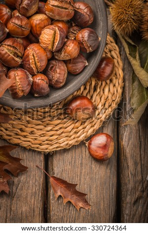 Roasted chestnuts on a rustic wooden table with autumn leaves in the background. - stock photo