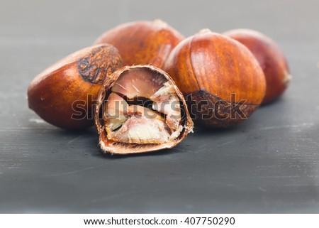 Roasted chestnuts on black - stock photo