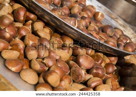 Roasted chestnuts on market stall. - stock photo