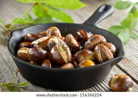 Roasted chestnuts on wooden background - stock photo