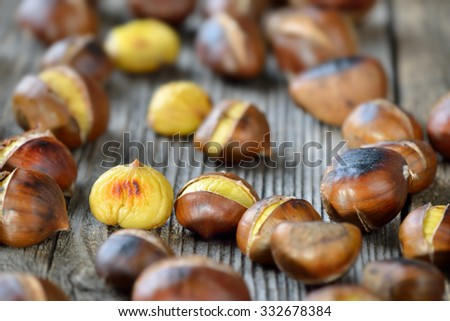Roasted chestnuts - ready to eat - on a rustic wooden table - stock photo