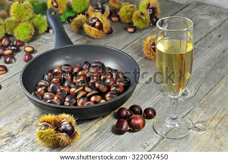 Roasted chestnuts with glass of white wine - stock photo