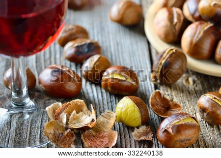 Roasted chestnuts with South Tyrolean red wine on an old wooden table - stock photo