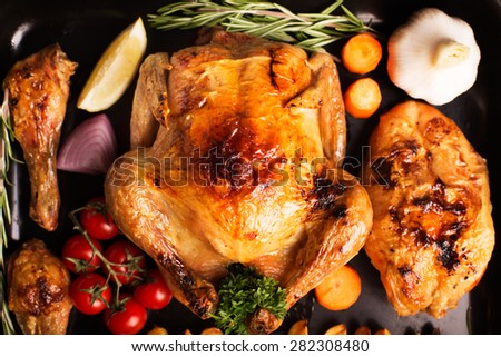 Roasted chicken and its shins, vegetables on the wooden table