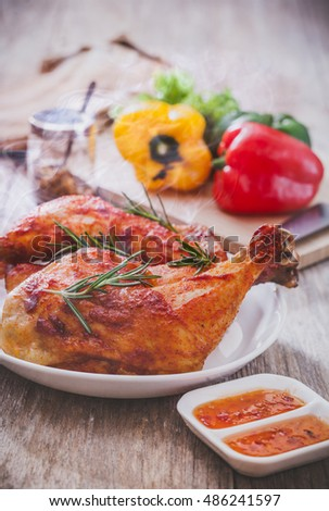 Roasted chicken and rosemary on table