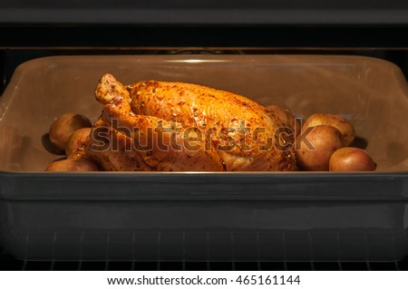 Roasted chicken and small potatoes in oven
